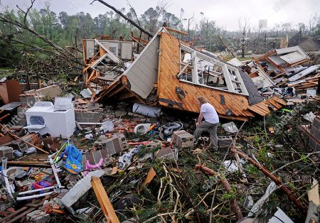 Kevin Barnes searches the remains of his home on Clayton Avenue in Tupelo, Miss., . A dangerous storm system that spawned a chain of deadly tornadoes over three days flattened homes and businesses, forced frightened residents in more than half a dozen states to take cover and left tens of thousands in the dark Tuesday