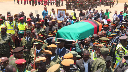 "Members of the Zambian Defence Forces and other government officials attend a ceremony to welcome the body of former Zambian President Michael Sata at Kenneth Kaunda International Airport in Lusaka, Saturday, Nov,1, 2014. Zambian President Sata dubbed ""King Cobra"" for his sharp tongued remarks died in a London hospital Tuesday after a long illness"