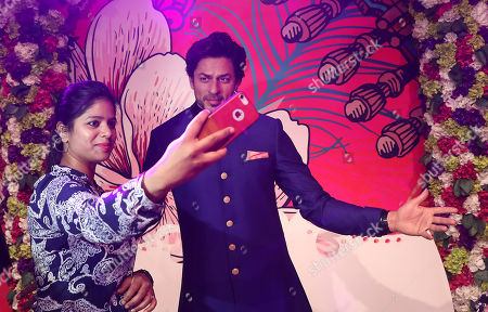 An Indian visitor takes a selfie with a newly launched wax figure of Indian Bollywood actor Shahrukh Khan at the Madame Tussauds wax museum in New Delhi, India, 04 April 2018. Madame Tussauds New Delhi features 50 wax figures of personalities from the fields of sports, music, film, history and politics.