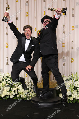 """Brandon Oldenburg, William Joyce. Brandon Oldenburg, left, and William Joyce, jump with their awards for best animated short film for """"The Fantastic Flying Books of Mr. Morris Lessmore"""" during the 84th Academy Awards, in the Hollywood section of Los Angeles"""