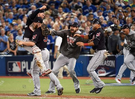 Cleveland Indians relief pitcher Cody Allen (37), cather Roberto Perez (55) and teammates Andrew Miller and Coco Crisp celebrate the team's 301 victory over the Toronto Blue Jays during Game 5 of the baseball American League Championship Series, in Toronto on