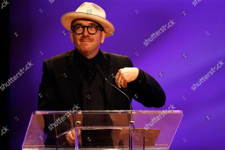 Elvis Costello smiles as he talks of his friendship during a funeral tribute to Allen Toussaint in New Orleans, . New Orleans and lovers of New Orleans' rich musical heritage crowded into the historic Orpheum theater Friday and bid goodbye in words and song to Toussaint, a prolific songwriter, performer and producer who died last week at age 77