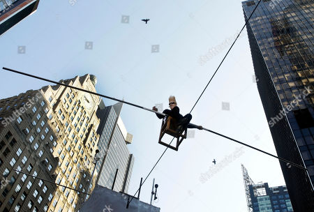 """Bello Nock, a seventh-generation circus performer, in an attempt to set a record for """"The Longest Continuous Interview on a Wire,"""" sits 27 feet above New York's Times Square, . This eight hour stunt kicks off the """"Summer of Bello"""" which will culminate on Aug. 30, when he will attempt to perform fifteen death defying stunts in Las Vegas"""