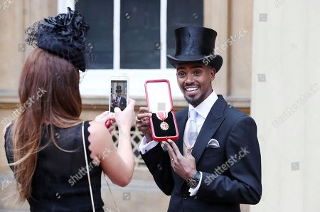 Four-time Olympic gold medalist Mo Farah poses for a photo, with his wife Tania, left, after he was awarded a Knighthood by Britain's Queen Elizabeth II at an Investiture ceremony at Buckingham Palace in London, . Farah is the most successful British distance runner track athlete in modern Olympic Games history
