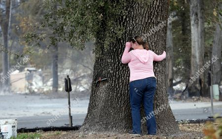 Deanna Hingst puts her arms on a massive tree and weeps outside the ashen remains of her family's home after finding the tree singed but apparently still healthy, in Middletown, Calif. Two of California's fastest-burning wildfires in decades overtook several Northern California towns, killing at least one person and destroying hundreds of homes and businesses and sending thousands of residents fleeing highways lined with buildings, guardrails and cars still in flames