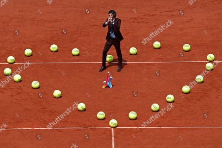 Former Brazilian tennis ace Gustavo Kuerten stands in the middle of a heart formed with large tennis balls prior to the men's final match between Stan Wawrinka and Spain's Rafael Nadal at the French Open tennis tournament at the Roland Garros stadium, in Paris, France