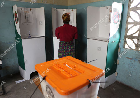 A woman casts her vote in a booth on election day, in Lusaka, Tuesday, Jan, 20, 2015, Candidates vying to replace Zambia's late President Michael Sata have cast their ballots along with thousands of other voters in Tuesday's presidential election