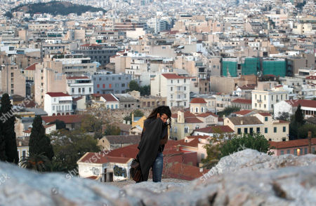 A tourist walks on a rocky outcrop above the city of Athens, background, on . Markets plunged Tuesday and Greece's beleaguered Socialist government faced collapse, a day after Prime Minister George Papandreou unexpectedly announced plans to hold a referendum on the latest international debt relief and bailout deal for his country