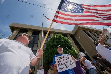 Tom Lowe, left, and James Perkins, with sign, show their support for Rowan County Clerk Kim Davis, at the United States District Court for the Eastern District of Kentucky in Ashland, Ky. A federal judge is hearing arguments Monday about Davis, one of a hand full of local officials across the country who are refusing to issue any marriage licenses after the U.S. Supreme Court's ruling legalizing same-sex marriage. The U.S. Supreme Court decided June 26 states cannot prohibit issuing marriage licenses to same-sex couples, but Davis has refused citing her religious beliefs