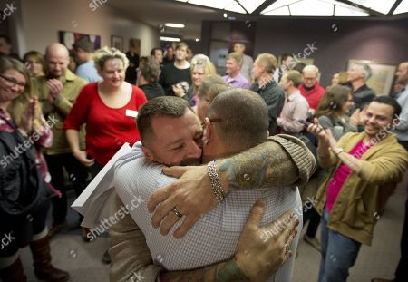 Stock Photo of Clifton Webb, Chris Serrano. Chris Serrano, left, and Clifton Webb embrace after being married, as people wait in line to get licenses outside of the marriage division of the Salt Lake County Clerk's Office in Salt Lake City. A federal judge on Monday, Dec. 23, 2013 is set to consider a request from the state of Utah to block gay weddings that have been taking place since Friday when the state's same-sex marriage ban was overturned