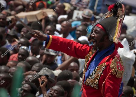 "A man dressed as Haitian National Hero Toussaint Louverture cheers during the inauguration ceremony for Haiti's President Michel Martelly, in front of the Haitian National Palace in Port-au-Prince, Haiti, . The 50-year-old performer known to Haitians as ""Sweet Micky"" was swept to power in a March 20 presidential runoff by Haitians tired of past leaders who failed to provide even basic services, such as decent roads, water and electricity in the Western Hemisphere's poorest country"