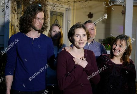 Amanda Knox, center, stands with her mother, Edda Mellas, right, and her fiance, Colin Sutherland, left, as she talks to the media outside Mellas' home, in Seattle. Italy's highest court overturned the murder conviction against Knox and her ex-boyfriend Friday over the 2007 slaying of Knox's roommate, bringing to a definitive end the high-profile case