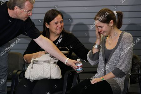 Amanda Knox, right, is offered water by her father Curt Knox as her mother, Edda Mellas looks on as they wait to talk to reporters, in Seattle. Knox was freed Monday after an Italian appeals court threw out her murder conviction for the death of her British roommate, Meredith Kercher