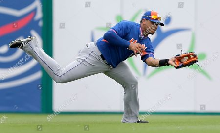 New York Mets center fielder Juan Lagares reaches out and catches a ball hit for an out by Miami Marlins' Jeff Baker during the third inning of an exhibition spring training baseball game, in Jupiter, Fla