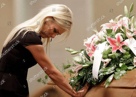 Jill Stancel places her hand on the casket of country music star Mindy McCready during the funeral ceremony at the Crossroads Baptist Church in Fort Myers, Fla., . McCready committed suicide Feb. 17 at her home in Arkansas, days after leaving a court-ordered substance abuse program