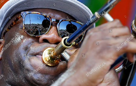 The crowd is reflected in the sunglasses of Big Sam, of Big Sam's Funky Nation, as he performs at the New Orleans Jazz and Heritage Festival in New Orleans