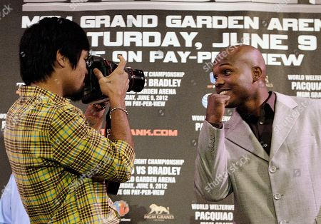 Manny Pacquiao, Timothy Bradley Jr. Manny Pacquiao, left, of the Philippines, uses a camera borrowed from a media member to photograph Timothy Bradley Jr. at a news conference, in Beverly Hills, Calif., to promote their June 9 welterweight boxing match in Las Vegas