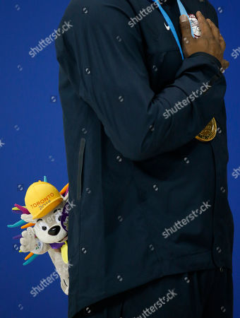 United States' Giles Smith holds a Pachi doll, the Pan Am Games mascot, during the medal ceremony after winning the gold medal in the the men's 100m butterfly final at the Pan Am Games in Toronto