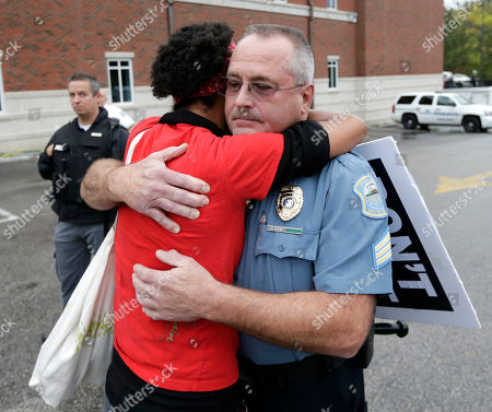 A woman who identified herself as Dragonfly, from the Brooklyn borough of New York, gets a hug from Ferguson, Mo., police Sgt. Michael Wood, after sharing her fear of police brutality with Wood, during a protest at the police station, in Ferguson, Mo. Activists planned a day of civil disobedience to protest the shooting of Michael Brown, in August, and a second police shooting in St. Louis last week