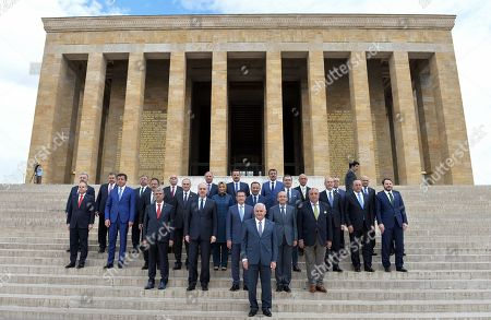 Turkey's new Prime Minister Binali Yildirim, front, and his ministers stand for a group photo as they visit the mausoleum of modern Turkey's founder, Mustafa Kemal Ataturk, after legislators voted 315-138 to approve his government, in Ankara, Turkey, . Turkey's new government, led by President Recep Tayyip Erdogan's loyal ally, has easily won a vote of confidence in parliament. Yildirim, 60, replaced former premier Ahmet Davutoglu, who stepped down after falling out of favor with Erdogan over a range of issues