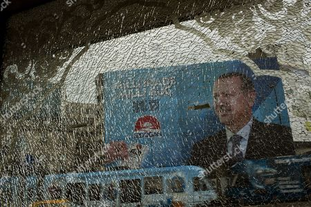 A poster of Prime Minister and presidential candidate in Turkey's Aug. 10 presidential election, Recep Tayyip Erdogan is seen through the broken glass of a nearby shop in downtown Istanbul, Turkey, . Turks vote Sunday in the country's first direct presidential election. Prime Minister Recep Tayyip Erdogan is widely seen as the front-runner in the race to replace Abdullah Gul. Other candidates are Ekmeleddin Ihsanoglu, the former chief of the Organization of Islamic Cooperation, and Kurdish politician Selahattin Demirtas
