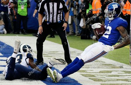 New York Giants wide receiver Tavarres King (12) catches a pass for a touchdown in front of Los Angeles Rams' John Johnson (43) during the first half of an NFL football game, in East Rutherford, N.J