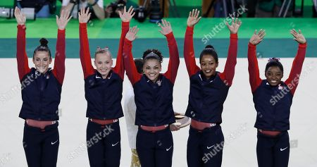 U.S. gymnasts and gold medallists, right to left, Simone Biles, Gabrielle Douglas, Lauren Hernandez, Madison Kocian and Aly Raisman raise their hands during the medal ceremony for the artistic gymnastics women's team at the 2016 Summer Olympics in Rio de Janeiro, Brazil