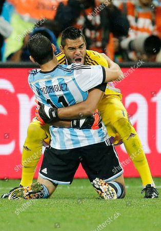 Maxi Rodriguez, Sergio Romero. Argentina's Maxi Rodriguez, front, celebrates with goalkeeper Sergio Romero after scoring the decisive goal during the World Cup semifinal soccer match between the Netherlands and Argentina at the Itaquerao Stadium in Sao Paulo, Brazil, . Argentina beat the Netherlands 4-2 in a penalty shootout to reach the World Cup final