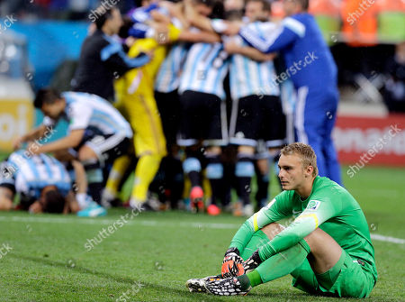 Netherlands' goalkeeper Jasper Cillessen sits on the ground after Maxi Rodriguez scored the winning goal during a penalty shootout after extra time during the World Cup semifinal soccer match between the Netherlands and Argentina at the Itaquerao Stadium in Sao Paulo Brazil, . Argentina defeated the Netherlands 4-2 in a penalty shootout after a 0-0 tie to advance to the finals