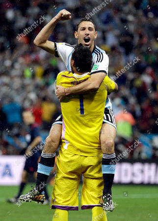 Argentina's Maxi Rodriguez celebrates with goalkeeper Sergio Romero after scoring the winning goal to give Argentina a victory over the Netherlands 4-2 in a penalty shootout after a 0-0 tie after extra time to advance to the finals during the World Cup semifinal soccer match between the Netherlands and Argentina at the Itaquerao Stadium in Sao Paulo Brazil