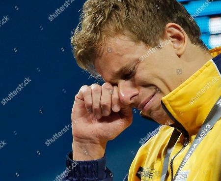Brazil's Cesar Cielo Filho wipes away tears after receiving his gold medal during the presentation ceremony for the Men's 50m freestyle final at the FINA Swimming World Championships in Barcelona, Spain