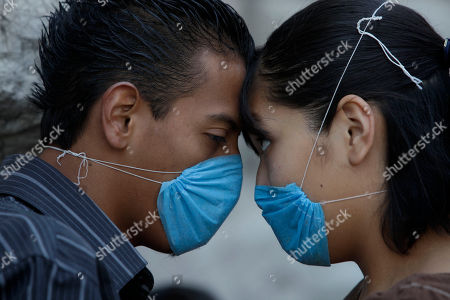 Stock Image of Wearing protective face masks to protect against swine flu contagion, Jaqueline Garcia Gonzalez, right, and Alan Martinez look at each other while waiting in line to be examined by a doctor at a mobile medical brigade set up in downtown Mexico City, Thursday April, 30, 2009