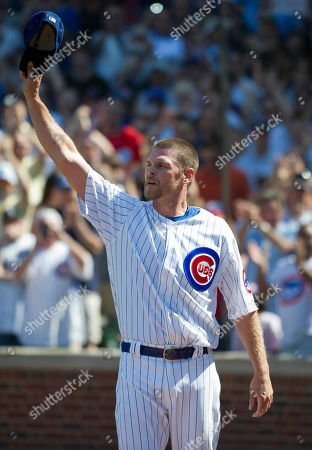 Chicago Cubs relief pitcher Kerry Wood tips his hat to the crowd after being taken out during the eight inning of a baseball game against the Chicago White Sox, in Chicago. The White Sox won 3-2. Wood faced one batter, striking out the White Sox's Dayan Viciedo, in what was likely his final appearance before retiring from baseball