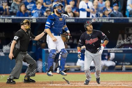 Home plate umpire Mike Everitt, left, Toronto Blue Jays catcher Russell Martin and Cleveland Indians' Coco Crisp watch Crisp's solo home run during fourth inning in Game 5 of baseball's American League Championship Series in Toronto