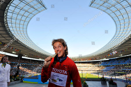 Germany's Steffi Nerius bites the gold medal she won in the Women's javelin during the medal ceremony at the World Athletics Championships in Berlin on