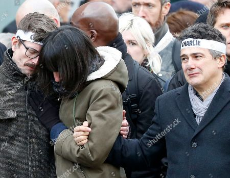 Charlie Hebdo newspaper staff, with editorialist Patrick Pelloux, right, cartoonist Renald Luzier, known as Luz, left, react during a march in Paris, France, . Thousands of people began filling France's iconic Republique plaza, and world leaders converged on Paris in a rally of defiance and sorrow on Sunday to honor the 17 victims of three days of bloodshed that left France on alert for more violence