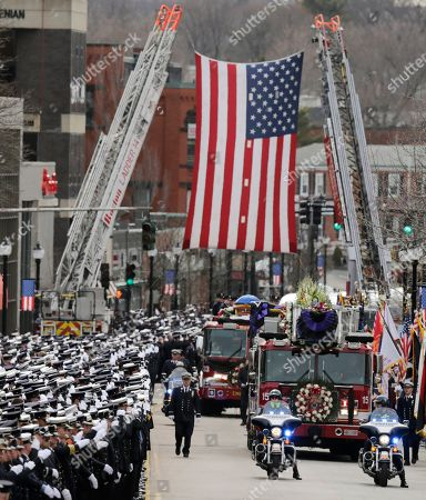 Firefighters salute as the funeral procession for Boston Fire Lt. Edward Walsh rolls under a flag spanning Main Street enroute to St. Patrick's Church in Watertown, Mass., . Walsh and his colleague Michael Kennedy died after being trapped while battling a nine-alarm apartment fire in Boston on March 26
