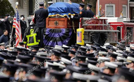 Firefighters salute as the casket of Boston Fire Lt. Edward Walsh is carried on Engine 33 as the funeral procession departs St. Patrick's Church in Watertown, Mass., . Walsh and his colleague Michael Kennedy died after being trapped while battling a nine-alarm apartment fire in Boston on March 26