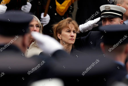 Firefighters salute as Kristen Walsh watches the casket of her late-husband Boston Fire Lt. Edward Walsh is lifted onto Engine 33 as the funeral procession prepares to depart St. Patrick's Church in Watertown, Mass., . Walsh and his colleague Michael Kennedy died after being trapped while battling a nine-alarm apartment fire in Boston on March 26
