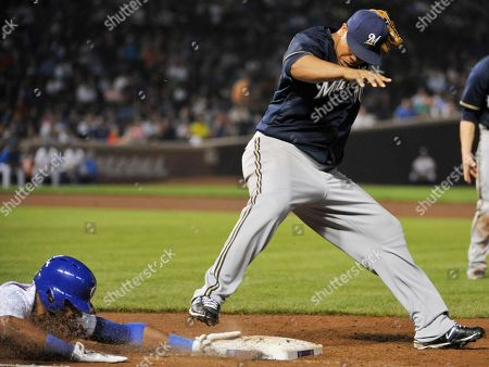 Julio Borbon,Wily Peralta. Chicago Cubs' Julio Borbon slides safely into first base on an error by Milwaukee Brewers first baseman Jonathan Lucroy as Milwaukee Brewers starting pitcher Wily Peralta tries to force him out during the fourth inning in a baseball game, in Chicago