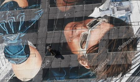 """A worker hangs on a rope to adjust a picture of Hollywood star Tom Cruise on the building to promote his latest movie """"Mission: Impossible - Ghost Protocol"""" in Seoul, South Korea"""
