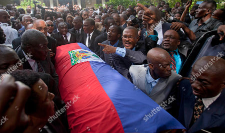 """Stock Image of Friends and family of Haiti's late Dictator Jean-Claude """"Baby Doc"""" Duvalier carry his flag draped coffin back to the funeral home after his funeral ceremony in Port-au-Prince, Haiti, . Many had wondered whether the self-proclaimed """"president for life"""" would receive a state funeral following his death last Saturday from a heart attack at age 63. However, friends and family held a simple and private funeral"""