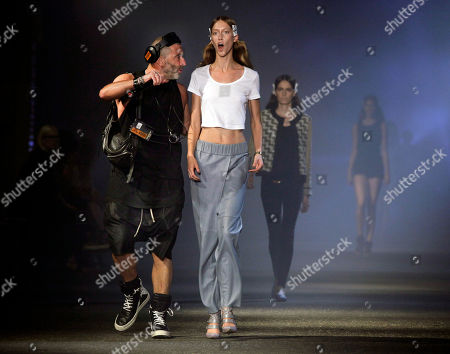 Fashion show producer Etienne Russo, left, from Brussels, schools a model during rehearsal for the Prabal Gurung Spring 2013 collection, during Fashion Week in New York