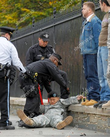 Lt. Dan Choi, center, falls as he is arrested for handcuffing himself to the fence outside the White House in Washington., during a protest for military gay-rights. The group demanded that President Obama keep his promise to repeal 'Don't Ask, Don't Tell
