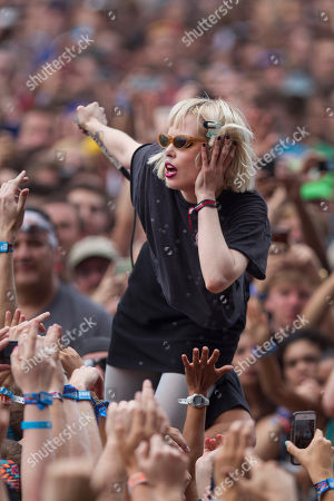 Alice Glass, vocalist for Canadian electronic band Crystal Castles interacts with fans after jumping off stage during their performance at the Lollapalooza Festival in Chicago, . The more than two-decade-old festival opens Friday in Chicago's lakefront Grant Park