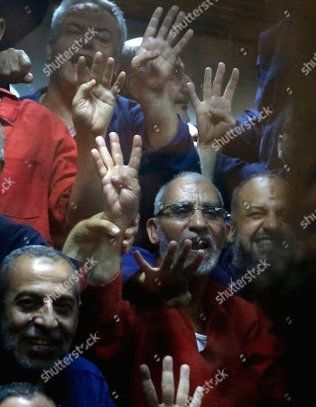 Egyptian defendants including the spiritual leader of the Muslim Brotherhood, Mohammed Badie, center, make a four-fingered gesture referring to the 2013 killing of Muslim Brotherhood protesters at the Rabaah Al-Adawiya mosque, in a makeshift courtroom at the Police Academy courthouse in Cairo, Egypt, . An Egyptian court on Tuesday confirmed a death sentence handed to Morsi over a mass prison break during the 2011 uprising that eventually brought him to power. On Tuesday a separate ruling upheld a life sentence for Morsi and confirmed death sentences against 16 others over charges of conspiring with foreign groups, including the Palestinian militant group Hamas. The judge also confirmed death sentences for five other jailed leading members of Morsi's Muslim Brotherhood, including Badie, the group's leader, and Saad el-Katatni, the head of its short-lived political party