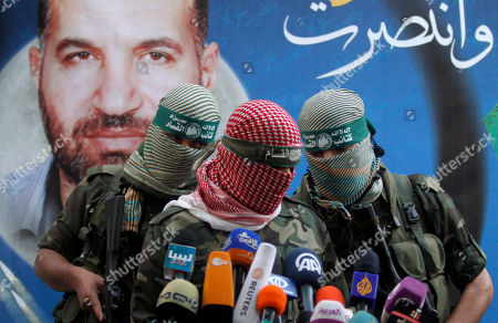 """A Hamas militant talks during a press conference in Gaza City, . Gazans are celebrating a cease-fire agreement reached with Israel to end eight days of the fiercest fighting in nearly four years constricting the Gaza Strip. The poster behind him reads: """"Gaza won"""" and shows the picture of Ahmed Jabari,a Hamas leader assassinated on Nov.14, setting off the last round of fighting between Israel and Hamas"""
