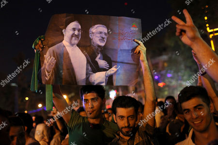 Stock Image of Iranians attend a street celebration, in Tehran, after their national soccer team qualified for the Brazil 2014 World Cup, after defeating South Korea, as they hold a poster of reformist former President Mohammad Khatami, left, and the Green Movement leader Mir Hossein Mousavi, who is currently under house arrest, on . The win set off wild celebrations across Iran, where the government had given a rare approval for supporters to spill into the streets. In separate messages, outgoing president Mahmoud Ahmadinejad and president-elect Hasan Rouhani congratulated the team for reaching the World Cup for a fourth time and first since 2006