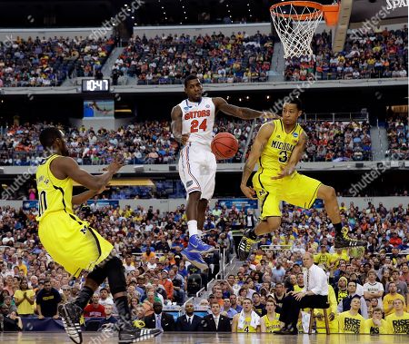 Tim Hardaway Jr., Casey Prather, Trey Burke. Michigan's Trey Burke (3) passes the ball to Tim Hardaway Jr. (10) in front of Florida's Casey Prather (24) during the second half of a regional final game in the NCAA college basketball tournament, in Arlington, Texas