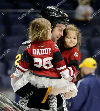 Pacific Division forward John Scott carries his children onto the ice after being named the most valuable player in the NHL hockey All-Star games, in Nashville, Tenn. The Pacific Division beat the Atlantic Division 1-0. Scott was elected as captain of the Pacific Division while with the Arizona Coyotes. He was traded to the Montreal Canadiens and he is now with the Canadiens' AHL affiliate in Newfoundland